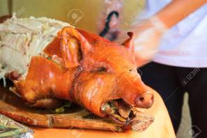 87837188-fried-pork-on-table-waiter-cut-whole-pork-traditional-dish-whole-roasted-pig-with-head-delicious-mea.jpg
